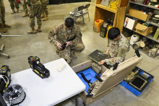 (From left) Staff Sgt. David Borgeson, team leader, and Spc. Lee Yoon, team member, 62nd Ordnance Company, demonstrate the assembly and disassembly of the SmartRayVision X1012 portable x-ray system, Jan. 16, 2018, at the 62nd EOD Headquarters, Fort Carson, Colo. The system is a new arrival to the unit's collection of EOD-specific equipment and is expected to replace the current system, the Science Applications International Corporation (SAIC) RTR-4, which has been in use for many years. (U.S. Army photo by Staff Sgt. Lance Pounds, 71st Ordnance Group (EOD), Public Affairs)