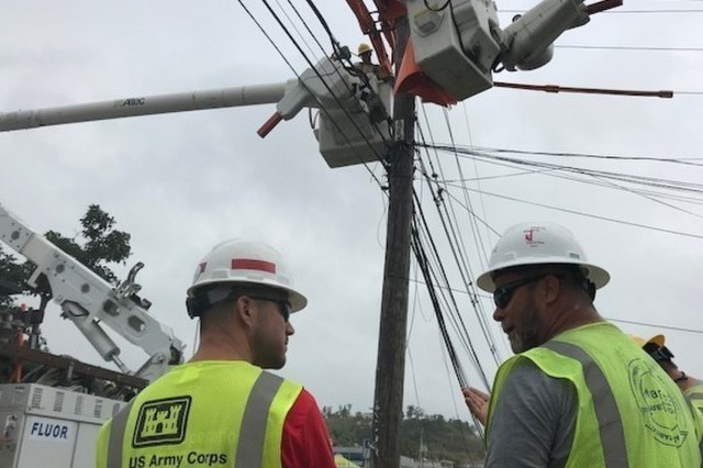 Kory Warrington a U.S. Army Corps of Engineers quality assurance specialist and Robert Harlow, a Mastec contractor, discuss safety procedures during distribution line repairs in Caya, Puerto Rico Jan. 25, 2018