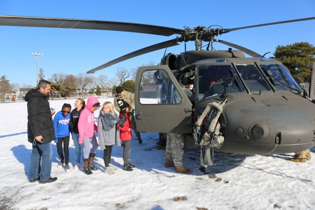 Students line up to explore a UH-60 Black Hawk helicopter courtesy of the U.S. Army Aviation Battalion Japan Jan. 25, 2018 for the STEM Symposium at Arnn Elementary. (U.S. Army photo by Lance D. Davis)