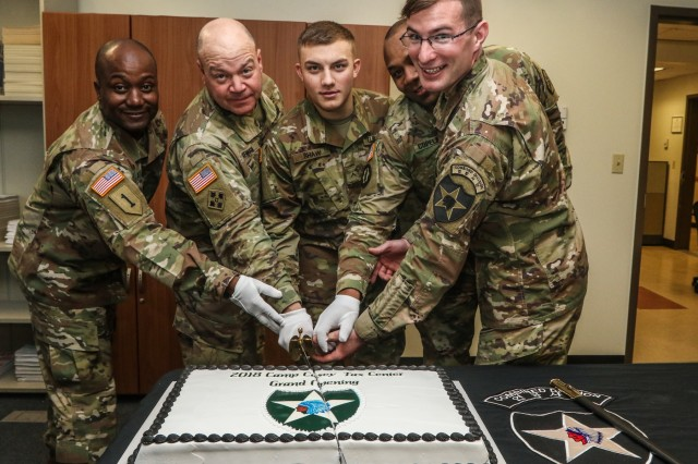 (Left to right) Lt. Col. Brian A. Jacobs, Commander, U.S. Army Garrison Casey, Col. Brandon D. Newton, Commander, U.S. Army Garrison Red Cloud and Area I, Pvt. Justin Shaw, Soldier with 210th Field Artillery Brigade, Command Sgt. Maj. Jason R. Copeland, U.S. Army Garrison Command Sergeant Major, and Capt. Jeremy Lewis, Tax Center officer in charge assigned to 2nd Infantry Division ROK/US Combined Division, cut a cake during the Camp Casey Tax Center Opening Ceremony at Maude Hall, Camp Casey, Republic of Korea, Jan. 25, 2018. (U.S. Army photo by Sgt. Michelle U. Blesam, 210th FA BDE PAO)