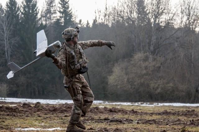 Spc. William Ritter, a military policeman with 287th Military Police Company, 97th Military Police Battalion, 89th Military Police Brigade, Fort Riley, Kansas, prepares to launch the RQ-11 Raven, small unmanned aerial system (SUAS), into the air during Allied Spirit VIII at Hohenfels, Germany, Jan. 26, 2018. Roughly 4,100 troops from 10 nations are participating in Allied Spirit VIII, a multinational training exercise designed to test participants' readiness and capabilities.