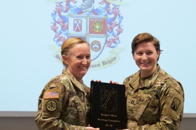 Col. Michelle Donahue, 16th Sustainment Brigade commander, presents a bowling competition award to Capt. Rebecca Deal, 627th Movement Control Team commander, in the Brigade Conference Room, Jan. 25. Deal won the bowling competition that took place as part of Knights Week, an annual event for company, battalion, and brigade leaders to come together to conduct leader development and team building activities.