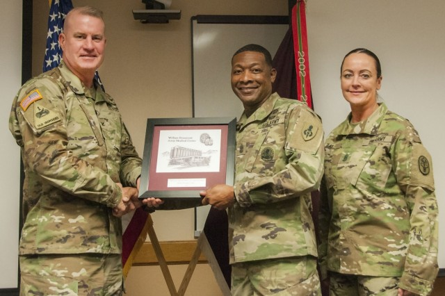 (From left) Col. Erik Rude, commander, William Beaumont Army Medical Center, Command Sgt. Maj. Reginald Gooden, deputy director and assistant dean of Sergeants Major Education, U.S. Army Sergeants Major Academy, Fort Bliss, Texas, and Command Sgt. Maj. Janell Ray, command sergeant major, WBAMC, take a photo as Rude presents a token of appreciation to Gooden during WBAMC's annual Martin Luther King Jr. Day observance at WBAMC, Jan. 19.