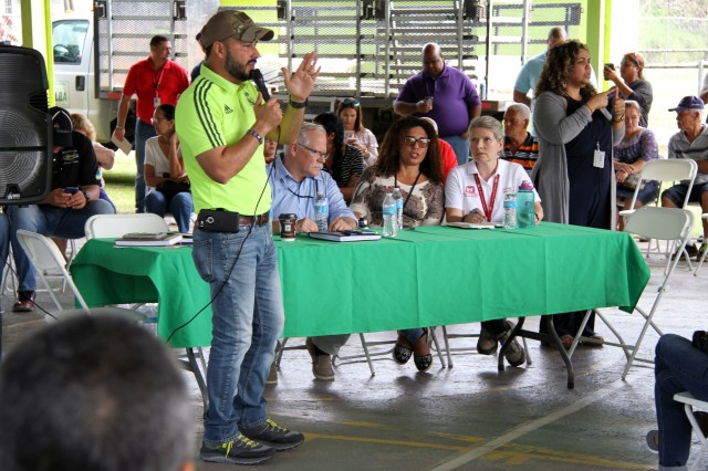 Villalba, Puerto Rico's Mayor Luis Javier Hernàndez spoke to a neighborhood meeting on January 27, 2018 about Hurricane Maria/Hurricane Irma response and recovery operations by the Federal Emergency Management Agency (FEMA), the U.S. Army Corps of Engineers and other federal agencies. Diane Kozlowski (seated at table on the right) serves as a Corps local government liaison for the area around Ponce in the south central part of Puerto Rico. FEMA Translator Lily Garcia (2nd from right at the table) shares the mayor's comments with her agency's representatives and Kozlowski.