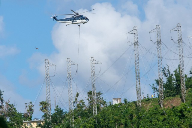 A contracted helicopter lifts power lines to towers as part of power restoration efforts in the mountain village of Trujillo Alto, Puerto Rico, Dec. 24, 2017. The U.S. Army Corps of Engineers, along with the Puerto Rico Electric Power Authority and other government agencies and contractors, have worked nonstop to restore power since the island was hit by two major hurricanes just two weeks apart in September.