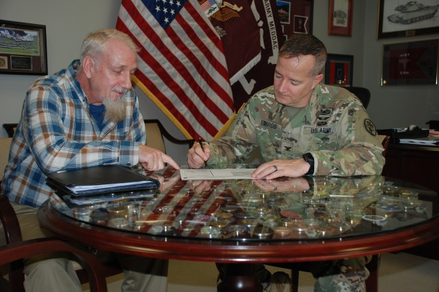 Jim Bonkowske, US Army Medical Activity Fort Jackson (MEDDAC FJ) Safety Officer reviews a recent safety report with COL Eric Edwards, MEDDAC FJ commander.