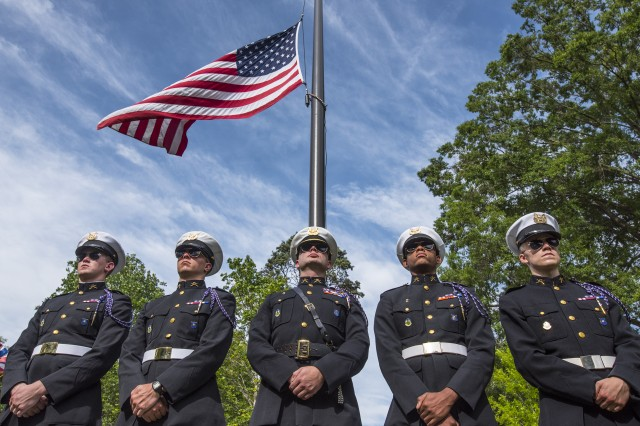 Clemson University ROTC cadets with the Clemson honor guard the Pershing Rifles stand under the American flag during a Memorial Day observance in Clemson's Memorial Park, May 28, 2017. U.S. Army Cadet Command is currently offering a $5k bonus for qualified sophomores who join ROTC.