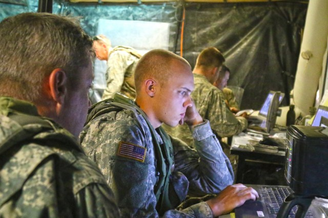 Spc. Clayton P. McInnis, a human intelligence analyst with 1st Battalion, 155th Infantry Regiment of the Mississippi Army National Guard, reviews reports in the unit's tactical operations center in June, at the National Training Center, Fort Irwin, California. The ExPED STO is designed to improve the conversion of large amounts of raw sensor data into usable situational understanding. (Mississippi National Guard photo by Staff Sgt. Shane Hamann, 102d Public Affairs Detachment)