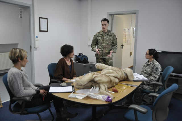 "Army Sgt. Jaden Cua (second from the right), animal care specialist at the Chièvres Veterinary Clinic, demonstrates how to use ""Jerry,"" a stuffed dog used for medical care training, to  Belgian Army Maj. Ann Jacob and Maj. Aniek De Smet, veterinarians at the Belgian Defence Veterinary Clinic, Jan. 25, 2018, at Caserne Daumerie in Chièvres, Belgium. The Chièvres Veterinary Clinic staff met with the Belgian Army veterinarians to discuss best practices for caring for military working dogs."