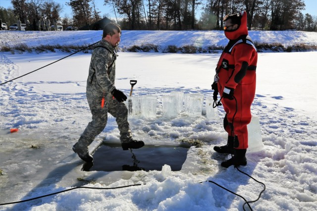 A Soldier participates in cold-water immersion training at an ice-covered Big Sandy Lake under the watchful eye of instructor Bill Hamilton as part of training for the Cold-Weather Operations Course on Jan. 17, 2018, at Fort McCoy, Wis. The Soldier was one of 25 students in the course. In addition to cold-water immersion training, students were trained on a variety of cold-weather subjects, including skiing and snowshoe training as well as how to use ahkio sleds and other gear. Training also focused on terrain and weather analysis, risk management, cold-weather clothing, developing winter fighting positions in the field, camouflage and concealment, and numerous other areas that are important to know in order to survive and operate in a cold-weather environment. The training is coordinated through the Directorate of Plans, Training, Mobilization and Security at Fort McCoy. (U.S. Army Photo by Scott T. Sturkol, Public Affairs Office, Fort McCoy, Wis.)