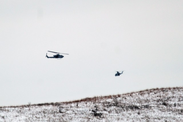 Two Marine Corps UH-1Y Venom helicopters at the installation for the 2nd Marine Aircraft Wing's Ullr Shield exercise fly near Young Air Assault Strip on South Post on Jan. 24, 2018, at Fort McCoy, Wis. Ullr Shield is a training exercise designed to improve 2nd Marine Aircraft Wing's capabilities in extreme cold-weather environments from early January to early February 2018. The 2nd Marine Aircraft Wing is headquartered at Marine Corps Air Station Cherry Point, N.C. Hundreds of Marines participated in the exercise at Fort McCoy. (U.S. Army Photo by Scott T. Sturkol, Public Affairs Office, Fort McCoy, Wis.)