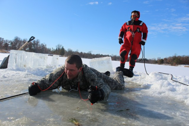 A Cold-Weather Operations Course Class 18-02 student participates in cold-water immersion training in frigid ice water at Big Sandy Lake on Jan. 17, 2018, at Fort McCoy, Wis. The students in this course class, all Soldiers from various active- and reserve-component units, learned about a variety of cold-weather subjects, including snowshoe training as well as how to use ahkio sleds and other gear. Training also focused on terrain and weather analysis, risk management, cold-weather clothing, developing winter fighting positions in the field, camouflage and concealment, and numerous other areas that are important to know in order to survive and operate in a cold-weather environment. The training is coordinated through the Directorate of Plans, Training, Mobilization and Security at Fort McCoy. (U.S. Army Photo by Scott T. Sturkol, Public Affairs Office, Fort McCoy, Wis.)