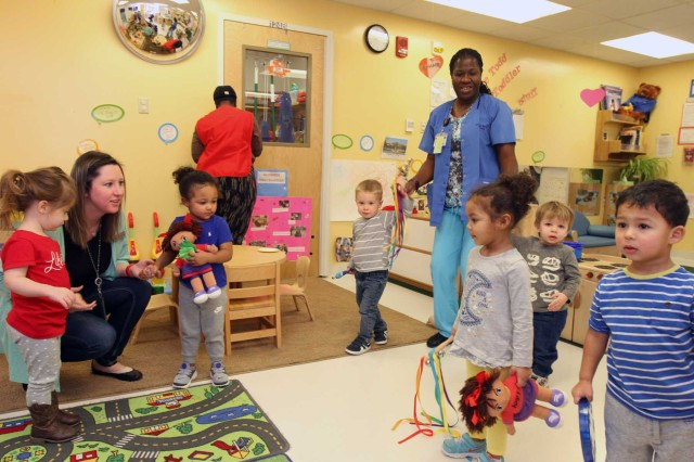 Lindsay Insomya (kneeling), Cooper Child Development Center director, and Sharon Harris (right), Lead Child and Youth Program assistant, take children through a marching dance Jan. 29, 2018,at Cooper CDC. The CDC was recently accredited by the National Association of the Education of Young Children. NAEYC accreditation requires child care centers to meet stringent requirements for curriculum, health standards, child supervision, staff training, family outreach, and facility maintenance.