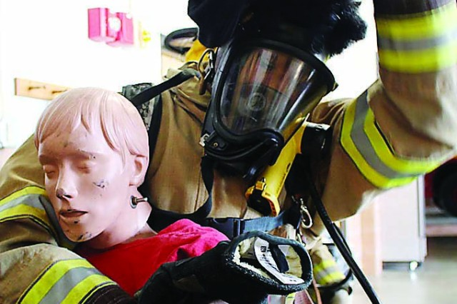 Fort Knox High School senior Jabari Jackson takes off a hood Monday that covered his mask during a search and rescue drill. The students had to rescue two dummies during the drill. The shroud covering his mask helped simulate low visibility in a smoke-filled room.