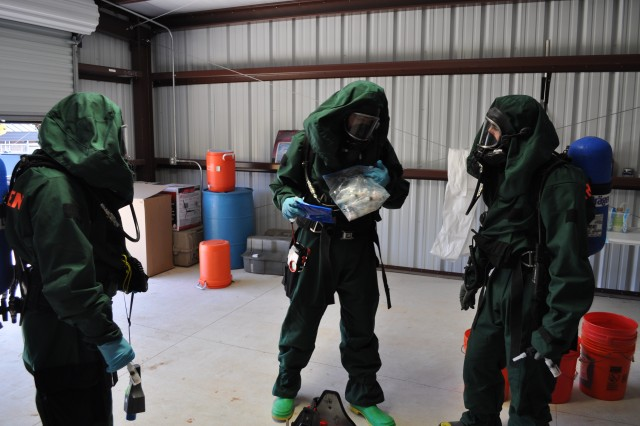 Members of the 4th Georgia Weapons of Mass Destruction Civil Support Team dressed in specialized protective gear prior to entering a mock scenario setup where they will layout a course of action for a chemical or biological response prepared by Special Programs Division's Mobile Training Teams from U.S. army Dugway Proving Ground, Utah.