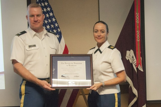 Col. Erik Rude, commander, William Beaumont Army Medical Center, and Command Sgt. Maj. Janelle Ray, command sergeant major, WBAMC, are presented a plaque representing WBAMC's Central Simulation Committee Medical Simulation Center's recent provisional accreditation from the Society for Simulation in Healthcare, an international medical simulation accrediting organization, at WBAMC, Jan. 26. The provisional accreditation is the first step toward full accreditation which is expected to welcome increased research and funding to WBAMC's simulation center, enabling Graduate Medical Education residents and current healthcare providers the ability to expand into evolving healthcare modalities.