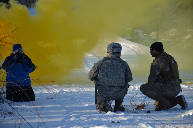 Devon Suits, left, Defense Media Activity, Army Media Gold Team, writer/editor, takes a photo as Sgt. 1st Class Fabio Herreradiaz, right, validates a student's charge emplacement during an Engineer Basic Officer Leader Course obstacle breaching exercise Jan. 17. DMA visited Fort Leonard Wood Jan. 16 through 19 to cover Army engineer careers and training.