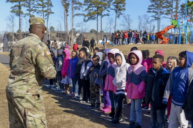 Spc. Kendell Smith, an Apache Helicopter mechanic 449th Theater Aviation Brigade, answers questions from students at Rogers Lane Elementary School in Raleigh, North Carolina, January 31, 2018. Kendell rode on the UH 72 Lakota Helicopter that landed on the school's field and talked to students about how helicopters work and gave the students an opportunity to see a helicopter up-close.