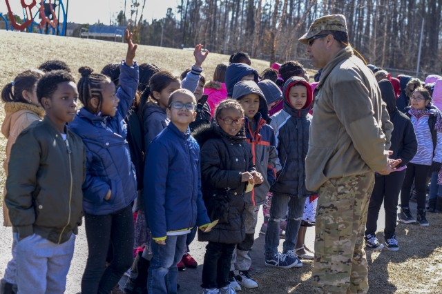 Chief Warrant Officer 5 Ty Mullins, a UH 72 Lakota Helicopter Pilot with the 449th Theater Aviation Brigade, talks to students at Rogers Lane Elementary School in Raleigh, North Carolina, after landing the Lakota Helicopter he piloted there, January 31, 2018. The school hosted the North Carolina National Guard helicopter and its crew as part of an enrichment program for the students. Soldiers answered questions about the aircraft and talked about the reading and math skills needed to both fly and conduct maintenance on helicopters.