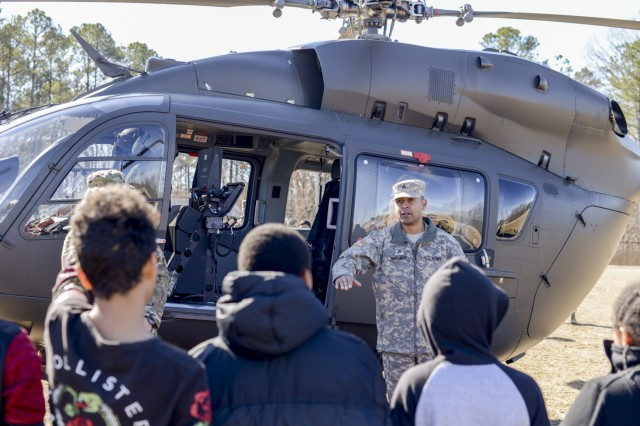 Sgt. Kevin Deharo Jimenez, an aircraft mechanic and crew chief with the 449th Theater Aviation Brigade, answers questions from students at Rogers Lane Elementary School in Raleigh, North Carolina, January 31, 2018. Dehire Jimenez and his team landed a UH 72 Lakota Helicopter on the school's field and talked to students about how helicopters work and gave the students an opportunity to see a helicopter up-close.
