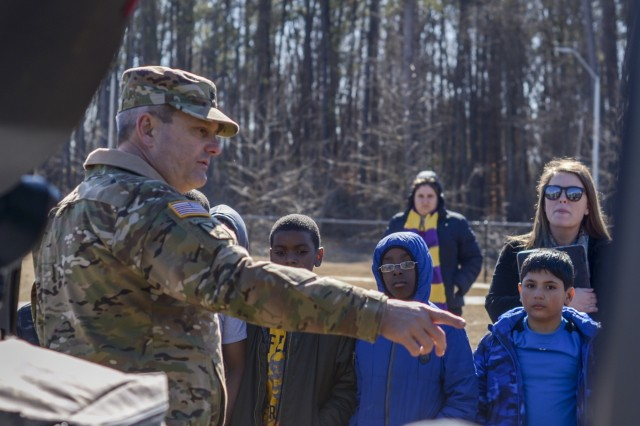 Lt. Col. Benny Collins, commander of the 1-130th Attack Reconnaissance Battalion, 449th Theater Aviation Brigade answers questions from students at Rogers Lane Elementary School in Raleigh, North Carolina, January 31, 2018. Soldiers with the 449th Theater Aviation Brigade landed a UH 72 Lakota Helicopter on the school's field and talked to students about how helicopters work, and the math and reading skills needed to be a pilot.