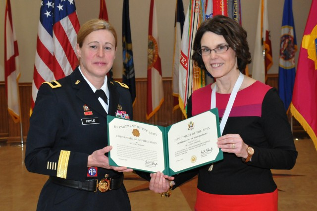 Brig. Gen. Heidi J. Hoyle, commander, Joint Munitions Command, presents Melanie Johnson her retirement certificate at the Rock Island Arsenal, Feb. 1.