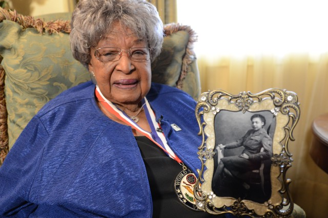 Millie Dunn Veasey wears her World War II medallion and shows a photo of her in uniform during World War II. The photo she holds was taken when she was stationed in England.