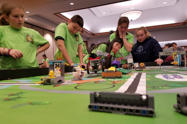 Team FLLow gathers around the table-top playing field before the competition begins at the FIRST LEGO League Maryland state qualifier tournament held at the Universities at Shady Grove in Rockville, Maryland, Jan. 6.