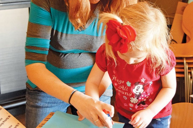 Alisha Salisbury, left, wife of Sgt. Michael Salisbury, Headquarters and Headquarters Company of 2nd Battalion 70th Armor Regiment, 2nd Armored Brigade Combat Team, 1st Infantry Division, and daughter Akayla, right, glue construction paper onto the care package for dad during the Hearts Apart Services for Waiting Families Program held at Fort Riley's Custer Hill Bowling Center Jan. 25.