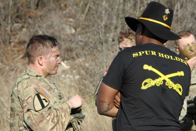 A Spur Holder from 6th Squadron, 9th Cavalry Regiment, 3rd Armored Brigade Combat Team, 1st Cavalry Division, observes Spur Candidates as they apply camouflage to their faces during the Squadron's Spur Ride, Jan 31. The Spur Ride consisted of an APFT, an obstacle course, 14 testing lanes and a Spur Ride testing the candidates Cavalry knowledge. (U.S. Army photo by Capt. Scott Kuhn, 3ABCT Public Affairs)