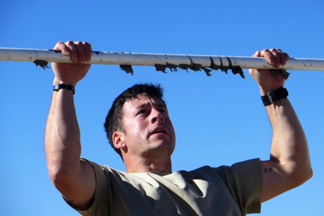 Capt. Rob Shalvoy, 304th Military Intelligence Battalion, begins his pull ups after carrying two full water cans around the physical training field and completing 50 pushups.