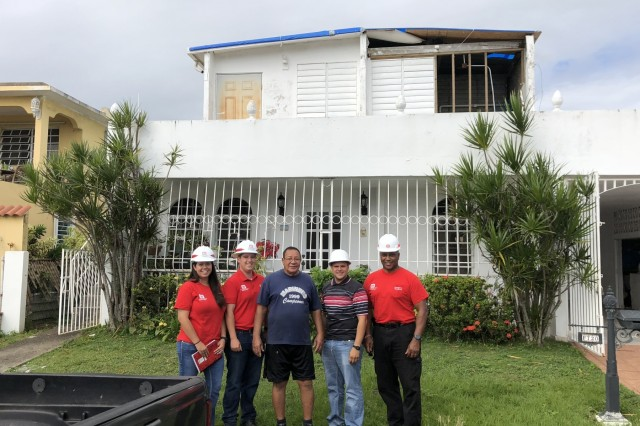 U.S. Army Corps of Engineers employees, a contractor and a Dorado, Puerto Rico citizen pose in front of his home with its completed blue roof installation on February 3, 2018. The home had only been partially habitable since hurricanes Maria and Irma caused massive damage to property on Puerto Rico in September 2017. From left to right, Jacksonville District's Rebecca Gray, Wilmington District's Chase Pattillo, the homeowner, translator Christian Ortiz, and the Engineer Research and Development Center's Fulton Carson. (Submitted photo from Wilmington District's Chase Pattillo)
