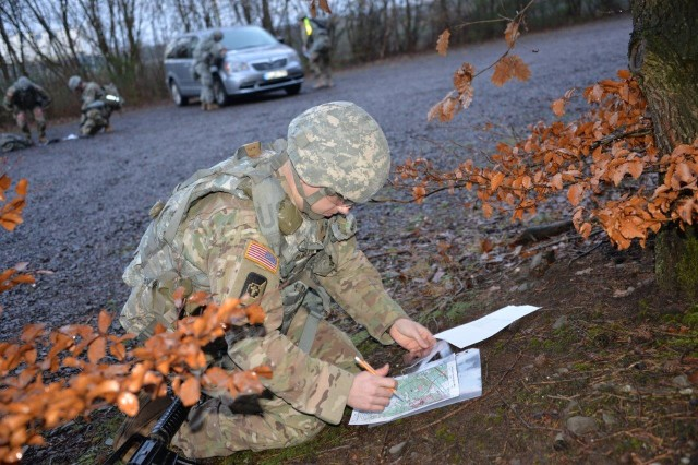 A Soldier plots grid coordinates on a map prior to beginning land nagivation during the USAMMCE/Public Health Command Europe Best Warrior Competition on Husterhoeh Kaserne, Jan. 29 -- Feb. 2.