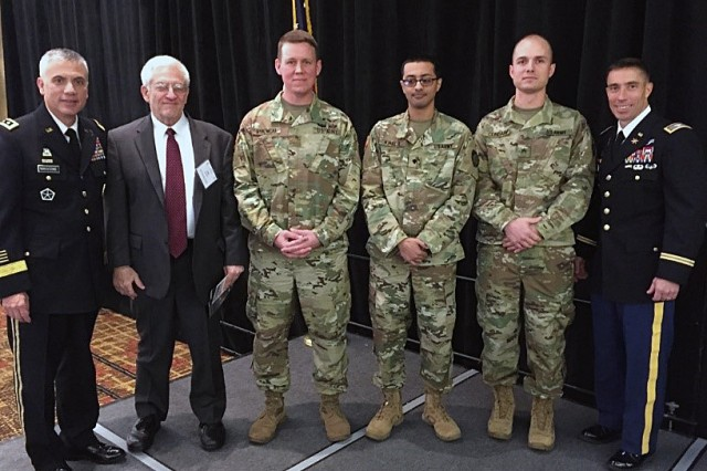 (Left to right) Lt. Gen. Paul Nakasone, commanding general, U.S. Army Cyber Command (left); Alan Paller, SANS founder and director of research (second from left); and Col. Paul Stanton, commander of the Army Cyber Protection Brigade (right), prepare to recognize the Army cyber team represented by team members (from left to right in field uniform) Maj. Josh Rykowski, Spc. Bishoy Khalil and Sgt. Matt Cundari, for the team's first-place win in the SANS NetWars Tournament of Champions in in Washington, D.C. in December 2017. The team was recognized during the Cyber Education, Research, and Training Symposium in Augusta, Ga., in January 2018.