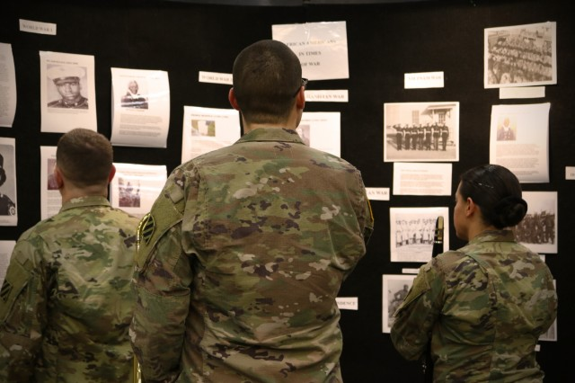Soldiers from 3rd Infantry Division look at a history board during a Black History Month Observance at Club Stewart, Fort Stewart, Ga., Feb. 1, 2018. The observance was held to educate and acknowledge the United States military for the strides it has made for equal rights of black Soldiers. (U.S. Army photo by Pfc. Zoe Garbarino, 50th Public Affairs Detachment, 3rd Infantry Division public affairs)