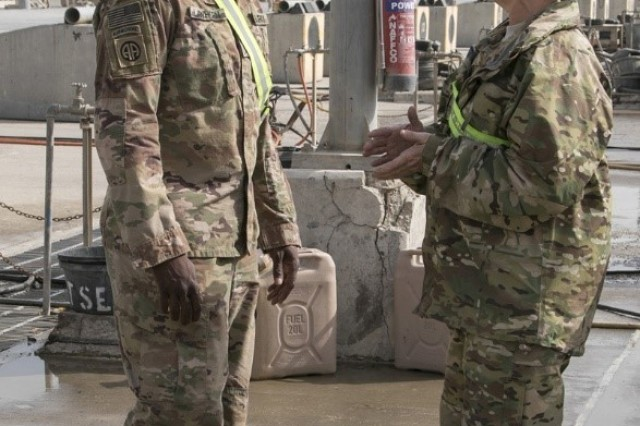 Sgt. Maj. Andre Lawhorn, 35th Infantry Division chemical, biological, radiological and nuclear sergeant major, takes a moment to talk to 35th Inf. Div. materials handler Staff Sgt. Mary Hunt about wash rack operations at Kuwait Naval Base, Jan. 24, 2018. Lawhorn believes that being on the ground with the troops while completing tasks is a crucial step in developing the Army's future leaders.