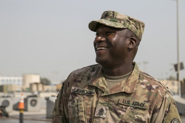 Sgt. Maj. Andre Lawhorn, 35th Infantry Division chemical, biological, radiological and nuclear sergeant major, enjoys a moment talking to his Soldiers during wash rack operations at Kuwait Naval Base, Jan. 24. Lawhorn believes that being on the ground with the troops while completing tasks is a crucial step in developing the Army's future leaders.