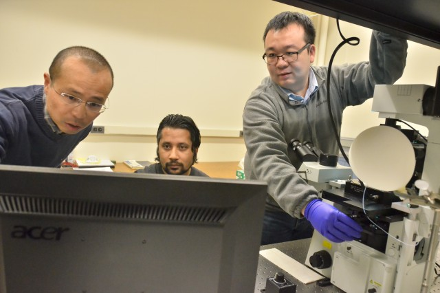 (L to R) Cornell University's Chemistry Professor Peng Chen, Principle Investigator and Dr. Susil Baral, Postdoctoral Research Associate, look at data on the instrument control computer while Dr. Chunming Liu, Postdoctoral Research Associate and lead author on the Science paper, adjusts the microscope stage on which the magnetic tweezers setup is operating.