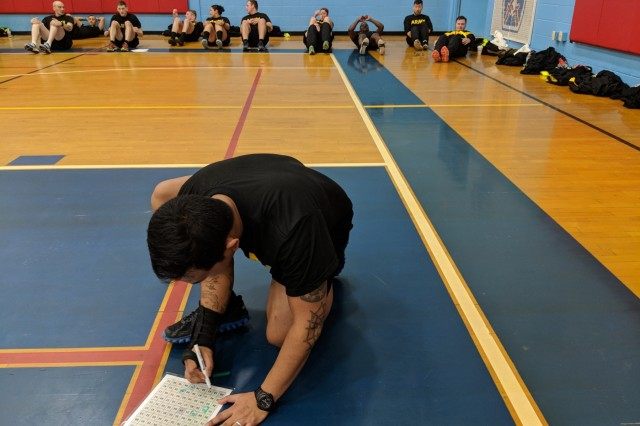 A Soldier from the 210th Brigade Support Battalion, 2nd Brigade Combat Team, 10th Mountain Division (LI), searches for a number on a grid while the rest of his group performs situps until the task is complete. Instead of their regular physical training session on the morning of Feb. 6, the group met with the Ready and Resilient Performance Center staff at Monti Physical Fitness Center for PT performance training.