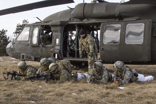 Spc. Marciel Cruz, a crew chief with C Company, 2-10 Assault Helicopter Battalion, 10th Combat Aviation Brigade, 10th Mountain Division (LI), instructs Soldiers on properly exiting a helicopter and establishing lines of fire at Fort Drum, New York, on February 2. The air assault operation lasted six days, with Aviators training and executing the air movement with three companies of Soldiers from 2nd Battalion, 87th Infantry Regiment, 2nd Brigade Combat Team, 10th Mountain Division (LI).
