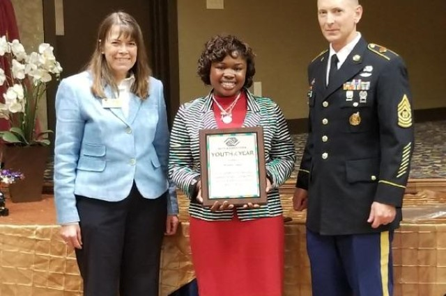 Rose Ann Turner, interim director of the Directorate of Family, Morale, Welfare and Recreation, and Command Sgt. Maj. John Drawbond, Garrison senior enlisted leader, stand with Winnie Tataw after she was named Youth of the Year for the second time.