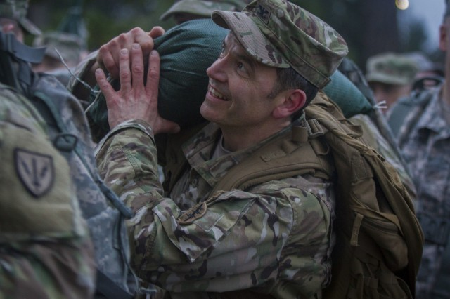 """A U.S. Army Soldier, assigned to I Corps, carries a 20 pound sand bag during the Value of Life Ruck March on Joint-Base Lewis-McChord, Wash., Feb. 1. The sand bags were a training tool representing the """"weight of life."""" As the ruck march drew to a close, the Soldiers were able to unload the sand bags with the help of their battle buddies. (U.S. Army photos by Pvt. Adeline Witherspoon)"""