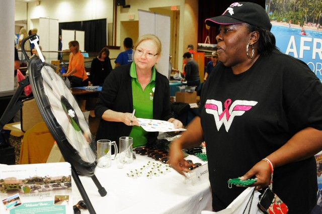 Karen Morris, military family member, takes on a spin game to try and win a prize at one of the vendor tables during the 30th annual Travel Extravaganza at The Landing Feb. 6.