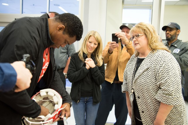 Winn ACH Infection Prevention and Control Specialist and longtime Walker fan, Stephanie Deloach, created a special table for Herschel Walker, and speaks with him as Winn ACH's risk management administration assistant, Cynthia Wilkinson looks on, during his recent visit to Fort Stewart.
