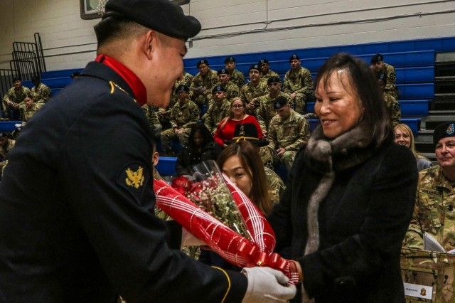 CAMP CASEY, Republic of Korea - Kyong Suk Kendall, the wife of Command Sgt. Maj. Cesar J. Zertuche, the outgoing command sergeant major of 1st Battalion, 38th Field Artillery Regiment, 210th Field Artillery Brigade, 2nd Infantry Division, ROK-US Combined Division receives a bouquet of red roses during a change of responsibility ceremony, Feb. 8. The red roses symbolize the heart, care and devotion to the Steel battalion. (U.S. Army photo by Pfc. Keonhee Lee, 210th FA Bde PAO)