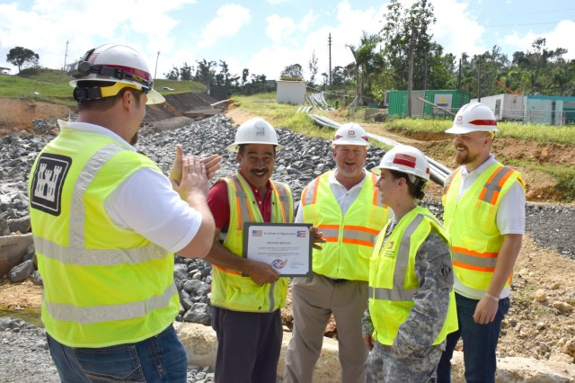 A certificate of appreciation was presented to Mr. Benito Belen, a local construction worker, by MAJ Kimberly Giles, Recovery Field Office Deputy Commander, for constructing a temporary bridge that allowed the Temporary Power Team to remove and install a new generator at the Guajataca Dam, restoring water to roughly 44,000 people, February 8, 2018.  After the original generator failed and needed replacement, contractors attempted multiple routes to try and get the new one installed, but they were unable to until the temporary bridge was created.