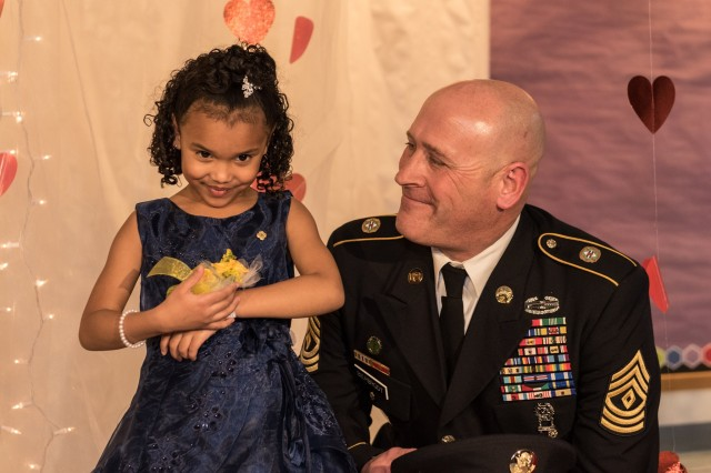 1st Sgt. Joseph Bierbrodt of Sheridan, Illinois, with the 933rd Military Police Company, smiles at Cayleigh Hinton just before escorting her into the father-daughter dance at the Our Lady of Humility School in Beach Park, Illinois, Feb. 7., Cayleigh's father, Sgt. Terrence Hinton, died in a training accident May 14, 2017 in Hawaii. Beirbrodt along with Cayleigh and her family were taken to the dance in a limo escorted by the Patriot Guard, multiple nearby police departments and fire departments.