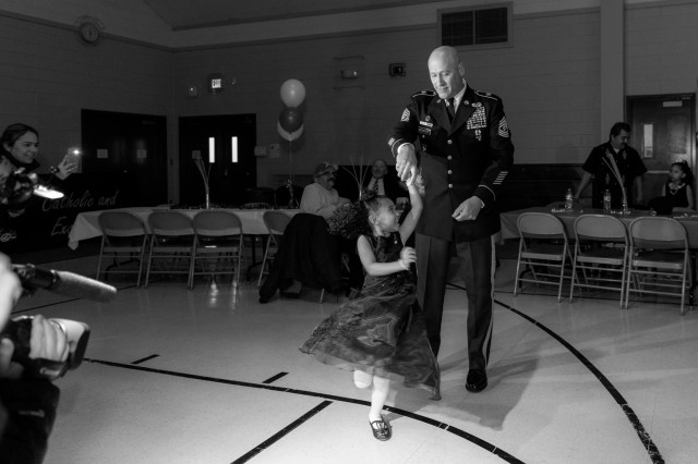 Cayleigh Hinton, daughter of Sgt. Terrence Hinton, dances with 1st Sgt. Joseph Bierbrodt of Sheridan, Illinois, with the 933rd Military Police Company, Feb. 7, at a father-daughter dance held at the Our Lady of Humility School in Beach Park, Illinois. Cayleigh's father, Sgt. Terrence Hinton, died in a training accident May 14, 2017 in Hawaii.
