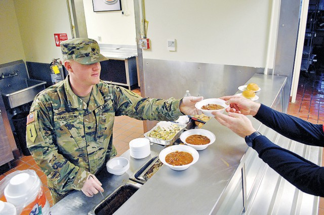 Spc. Delano Vankuren, Headquarters and Headquarters Company, 1st Combat Aviation Brigade, 1st Infantry Division, and president of Better Opportunities for Single Soldiers, serves up some chili and bread at the USO Fort Riley No Dough Dinner at the Culinary Lab Jan. 30. Vankuren was volunteering on behalf BOSS at the event.