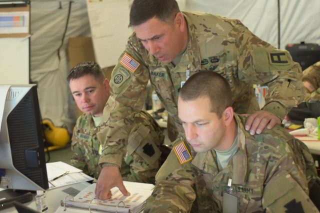 "Lt. Col. William Baker (standing), a medical observer coach/trainer with First Army's 120th Infantry Brigade, talks with Capt. Matt Gabler, medical logistics officer for the Pennsylvania Army National Guard's 28th Infantry Division, during the 28th ID's culminating training exercise at Fort Hood, Texas, Jan. 30, 2018. ""(The 28th ID's) surgeon section is pretty robust, across the board, which will help them out eventually. They're engaged, building maps and looking at medevac routes,"" said Baker, one of dozens of First Army personnel supporting the CTE before the 28th ID deploys to the Middle East. ""Right off hand, I think they're doing a great job,"" he said. ""I think they'll have a good deployment.""Gabler, from DuBois, Penn., has an unusual civilian career: he represents the state's 75th District in the Pennsylvania House of Representatives. ""I'm glad to be able to do what I trained for,"" he said. ""To receive the call to do a real-world mission is a great honor.""(Photo altered for security purposes.)"